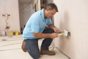 Electrician repairing outlet