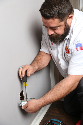 Electrician repairing power outlet